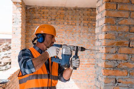 handsome bearded man using hammer drill near brick wall Reklamní fotografie