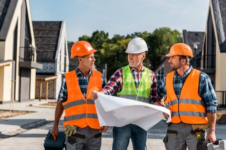 mature builder holding blueprint near coworkers and houses