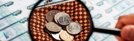 panoramic shot of man holding magnifier near coins in plaid wallet near russian money 写真素材