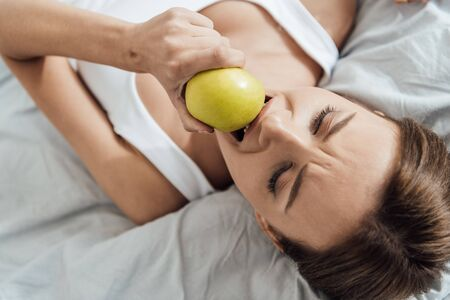 overhead view of upset young woman eating green apple in bed