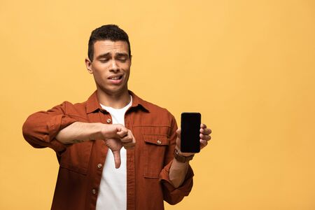 confused mixed race man showing smartphone with blank screen and thumb down isolated on yellow Foto de archivo - 131260433