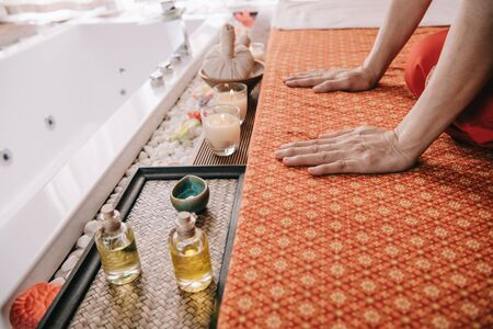 cropped view of masseur sitting on massage mat in spa Stock Photo