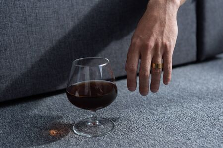 partial view of man with ring and glass of cognac