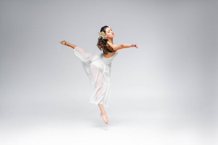 young graceful ballerina dancing in white dress on grey background