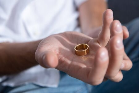 partial view of man holding ring at home