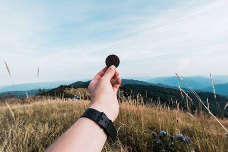 cropped view of man holding sweet cookie in field near mountains Foto de archivo