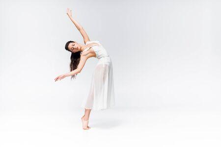 Hermosa bailarina en vestido blanco bailando con los ojos cerrados sobre fondo gris