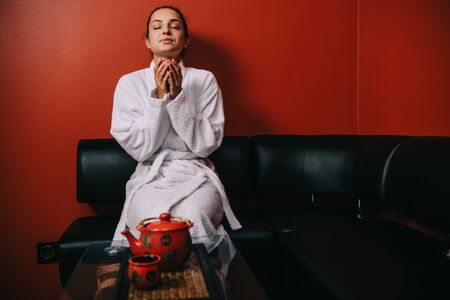 attractive woman in white bathrobe with closed eyes sitting on sofa and holding cup
