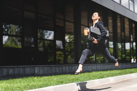 happy businesswoman levitating while holding briefcase and coffee to go Stock fotó