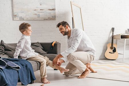 smiling father helping son to get dressed at home