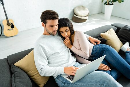 african american woman and handsome man looking at laptop Stock Photo