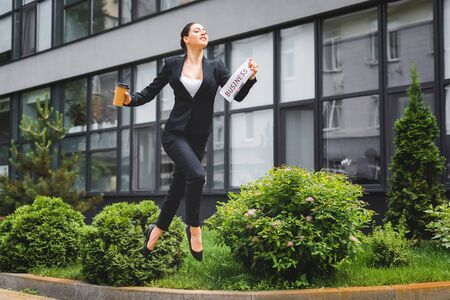 graceful businesswoman levitating while holding newspaper and paper cup