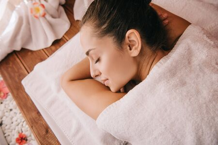 attractive woman with closed eyes lying on massage mat