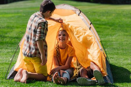boy looking at happy friend sitting in camp