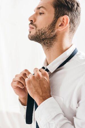 serious bearded man in white shirt tying tie