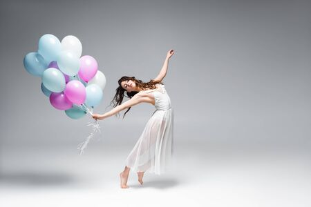 young, beautiful ballerina dancing with festive balloons on grey background