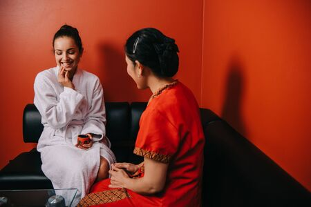 smiling woman and masseur in costume sitting on sofa in spa salon Stock Photo