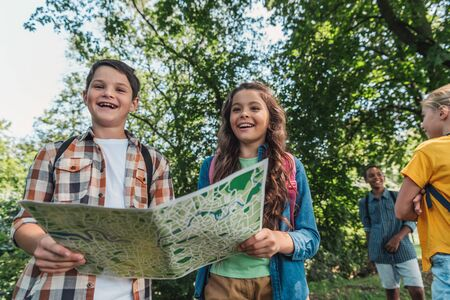 selective focus of happy kids holding map near multicultural friends