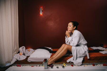 attractive woman with closed eyes in bathrobe sitting on massage mat in spa salon