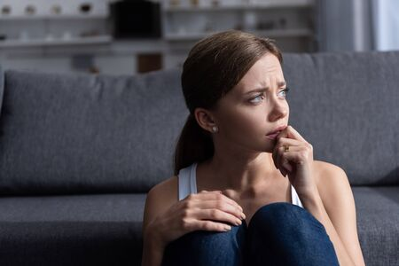 upset young woman with ring sitting near sofa in living room at home Stockfoto