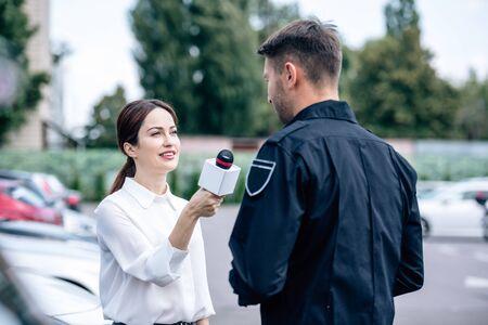 Periodista sosteniendo el micrófono y hablando con un policía guapo en uniforme Foto de archivo