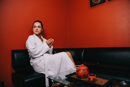 attractive woman in white bathrobe sitting on sofa and holding cup Stock Photo