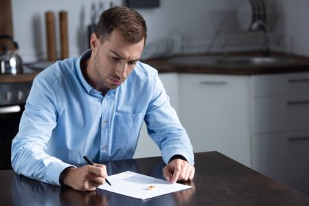 sad man in shirt sitting at table with ring and signing divorce documents