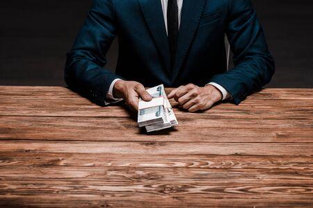 cropped view of man holding russian money near desk Zdjęcie Seryjne