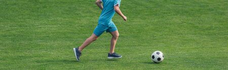 panoramic shit of kid in sportswear running on green grass with football