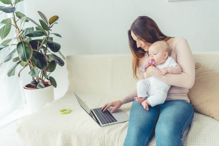 attractive mother holding her child and using laptop in apartment 免版税图像