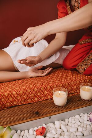 cropped view of masseur pouring fragrance oil on hand and woman lying on massage mat Stock Photo