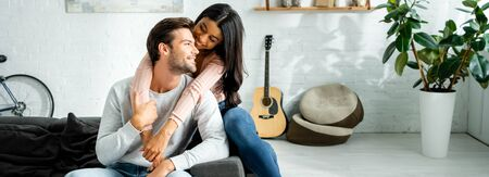 panoramic shot of african american woman and handsome man smiling and hugging in apartment Banco de Imagens