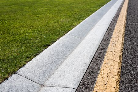 close up of border on road near green and fresh grass Stock Photo