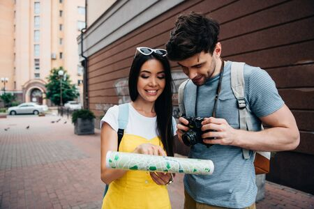handsome man with digital camera and asian woman looking at map
