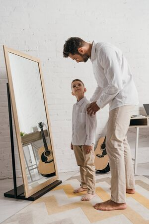 full length view of barefoot father and son standing near mirror