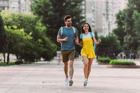 handsome man and asian woman running and looking away
