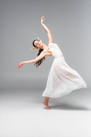 Elegante y atractiva bailarina en vestido blanco bailando sobre fondo gris Foto de archivo