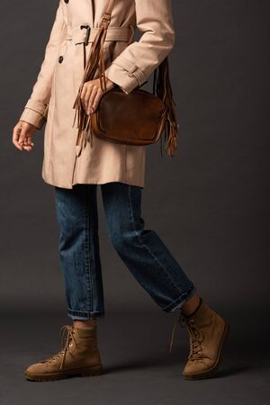 cropped view of stylish woman in trench coat with leather brown bag on black background