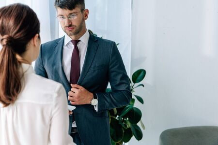 back view of journalist talking with businessman in formal wear