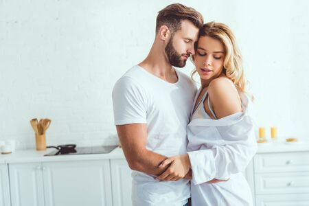 happy young couple embracing with closed eyes in kitchen