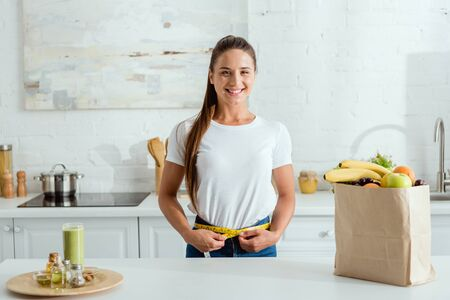 cheerful young woman measuring waist near paper bag with groceries Stok Fotoğraf