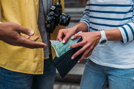 Cropped view of woman checking money in wallet near bi-racial friend