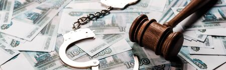 panoramic shot of wooden gavel near handcuffs on russian money Stock Photo