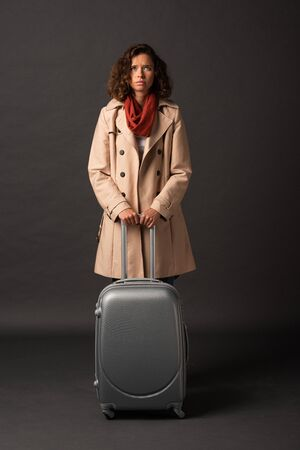 upset elegant woman in trench coat and scarf holding handle of suitcase on black background Stockfoto