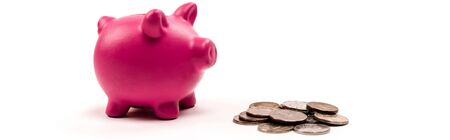 panoramic shot of pink piggy bank near silver and golden coins on white