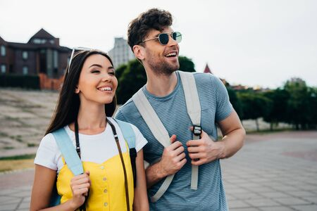 handsome man and asian woman with backpacks looking away