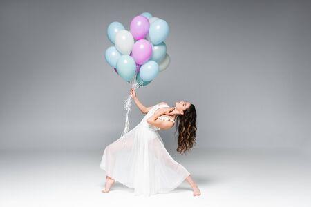 Hermosa joven bailarina en vestido blanco bailando con globos festivos sobre fondo gris