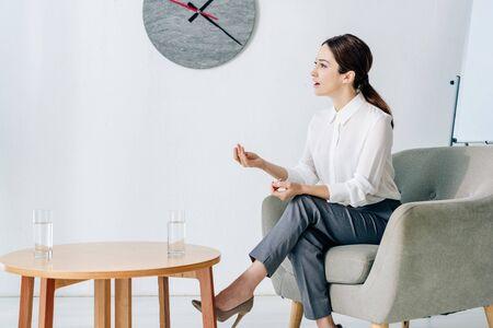 attractive journalist in formal wear sitting in armchair in office