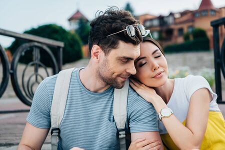 asian woman with closed eyes lying on shoulder of handsome man