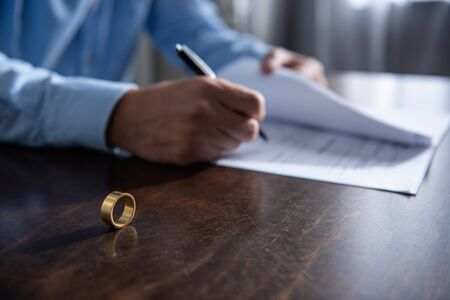 partial view of man sitting at table and signing divorce documents